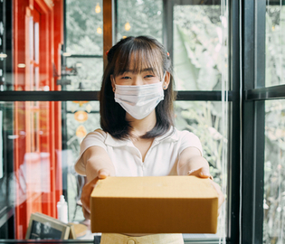 female delivering a package and wearing a mask